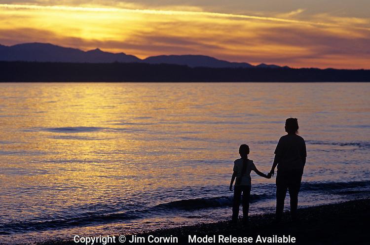 Mother and daughter holding hands along Edmonds Beach at sunset Edmonds Washington State USA