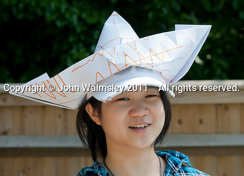 Wearing a paper hat she'd just made, Summerhill School, Leiston, Suffolk. The school was founded by A.S.Neill in 1921 and is run on democratic lines with each person, adult or child, having an equal say.  You don't have to go to lessons if you don't want to but could play all day.  It gets above average GCSE exam results.