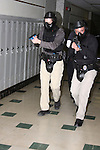 Male police officers in training holding a paint ball simulated gun clearing a hallway in a school shooting scenario