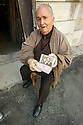 An old artisan having a break in front of his workshop shows an old picture of him and his wife.