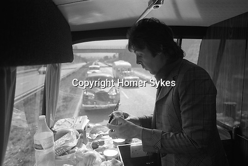 "Paul and Linda McCartney Wings Tour 1975. Paul making a sandwich at the back of the tour bus. He has two Rolls Royce cars following behind the coach, for his use should he need them. The photographs from this set were taken in 1975. I was on tour with them for a children's ""Fact Book"". This book was called, The Facts about a Pop Group Featuring Wings. Introduced by Paul McCartney, published by G.Whizzard. They had recently recorded albums, Wildlife, Red Rose Speedway, Band on the Run and Venus and Mars. I believe it was the English leg of Wings Over the World tour. But as I recall they were promoting,  Band on the Run and Venus and Mars in particular."