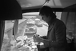 Paul and Linda McCartney Wings Tour 1975. Paul making a sandwich at the back of the tour bus. He has two Rolls Royce?s following behind the coach, for his use should he need them.