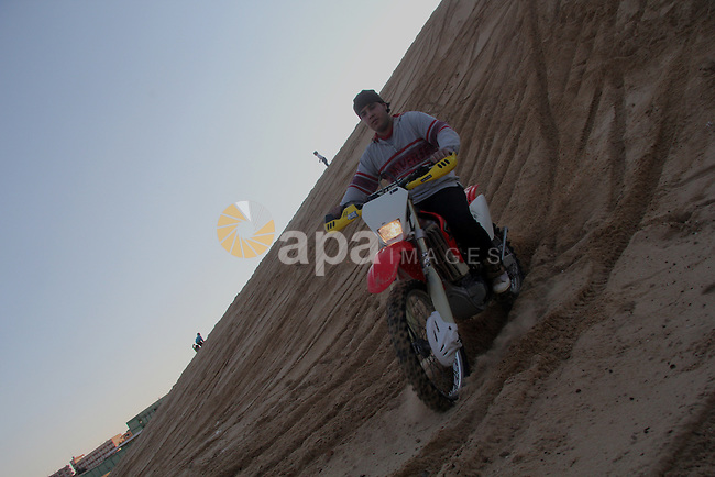 A Palestinian youth rides his motorcycle on sand dunes during the weekly sport event in the Gaza Strip of al-Zahra town, south of Gaza City, on Jan. 12, 2013 Palestinian youths use the dunes for riding their motorcycles, horses, cars and bicycles. Photo by Ezz al-Zanoon