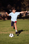 Boy playing soccer in the park - authrntic action - copy space