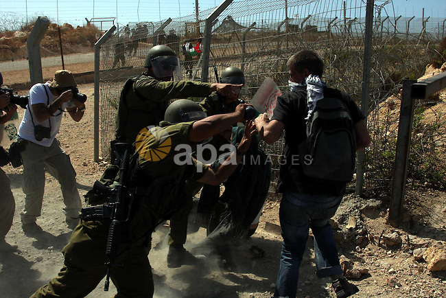 Israeli soldiers scuffle with a protester during a protest against the controversial Israeli barrier in the West Bank village of Bilin near Ramallah on Sep 25, 2009. Photo by Issam Rimawi