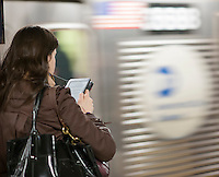 A woman with her Amazon Kindle electronic book reader waits for a train in a subway station in New York on Tuesday, February 12, 2013. (© Richard B. Levine)