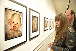 Huntington, New York, U.S. - March 1, 2014 - GAIL NELSON and BILLY NELSON, of Freeport, look at the humorous artwork of a baby doll sticking out its tongue, in the 'Vitreous Humor – A Collection of Absurd Images' exhibit that combines photos of dolls with vintage medical illustrations, by artist Lois Youmans at the FotoFoto Gallery Opening Reception 'Artists reception '3 Wild & Crazy Artists.'