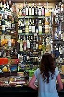 Young girl at liquor store and souvenir shop in Santiago de Compostela, Galicia, Spain