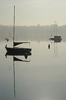 Two sailboats sit on the calm water of Lake Nokomis on a misty summer morning.