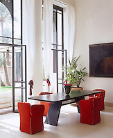 Red dining chairs bring a splash of colour and sophistication to this otherwise black and white dining area
