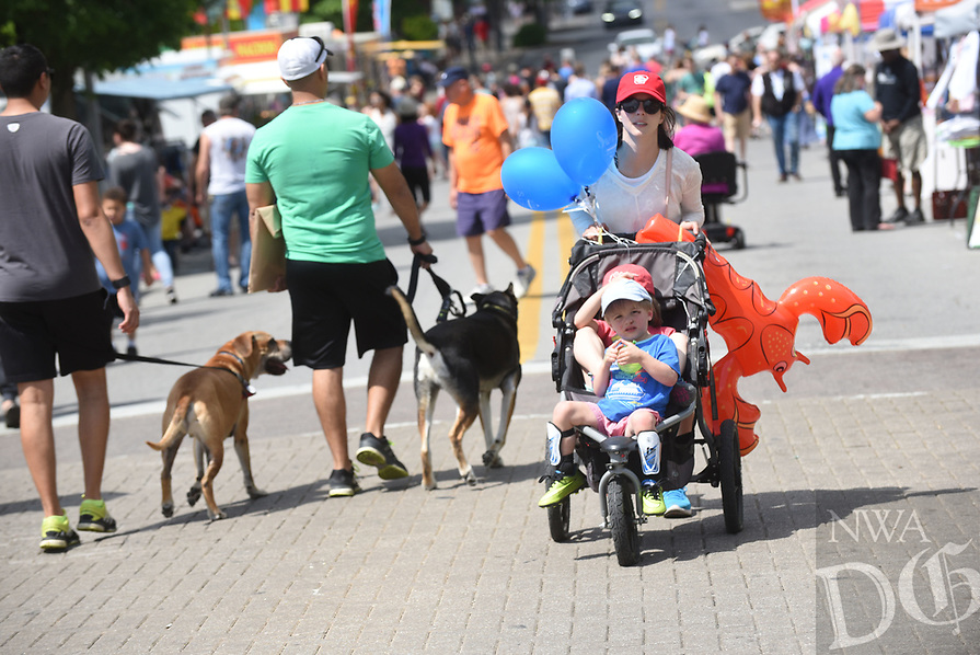 NWA Democrat-Gazette/FLIP PUTTHOFF <br /> SPRINGFEST STROLL<br /> Beth Saviers of Fayetteville pushes her children Russell Saviers, 3, (front of stroller) and Mary Collins Savier, 4 (in back seat) along Dickson Street on Saturday April 15 2017 during the annual Springfest celebration. The event included bed races, a pet parade, 5-kilometer run, vendor booths, music and more. The event was started in 1983 by Dickson Street merchants to celebrate the history, culture and flavor of Fayetteville.
