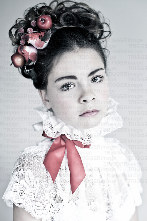 Female youth with dark curly hair wearing a white lace top with red ribbon and birds