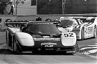 MIAMI, FL - MARCH 2: The Hendricks Motorsports Lola T710 HU1/Corvette GTP of  Sarel van der Merwe and Doc Bundy is driven ahead of the Brun Motorsport Porsche 962 107B of Massimo Sigala and Oscar Larrauri during the Lowenbrau Grand Prix of Miami IMSA GTP race on the temporary street circuit in Bicentennial Park in Miami, Florida, on March 2, 1986.