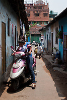 Razia Shabnam (in blue) reaches home through the alleyways of Ekbalpore after she picks her son, Saihaan, up from the St. Thomas School in Kidderpur after finishing her boxing training sessions in Calcutta, West Bengal, India. Razia Shabnam, 28, was one of the first women boxers in Kolkata. She was also the first woman in her community to go to college. She is now a coach and one of only three international female boxing referees in India.  Photo by Suzanne Lee for Panos London