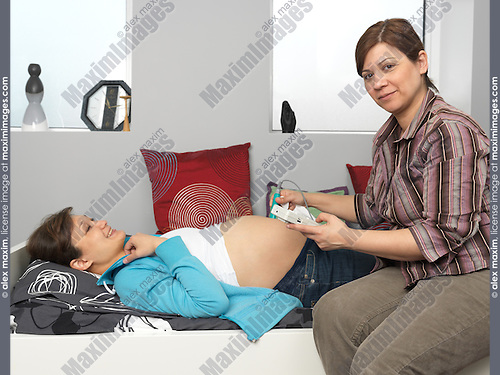 Midwife checking a pregnant woman's baby heartbeat with a doppler fetal monitor