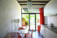 The deep orange curtains and plastic chairs sound a bright note of contrast in the kitchen where metal ceiling beams and concrete walls have been left minimally bare