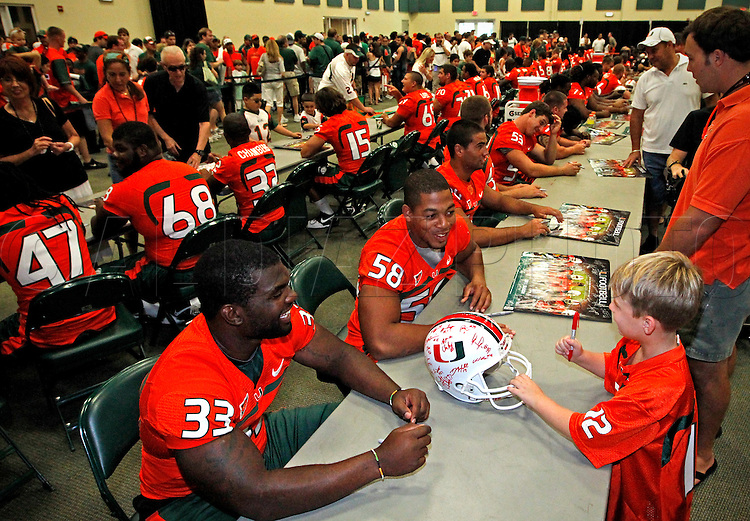 Maurice Hagens and Jordan Futch talk with fan Seth Stewart, 6, as he looks for autographs during CanesFest  for the University of Miami Football team on Campus in Coral Gables on August 27, 2011.