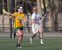 Boston College midfielder Kristin Igoe (21) brings the ball forward as University of Vermont midfielder Marcie Marino (16) pressures. Boston College defeated University of Vermont, 15-9, at Newton Campus Field, April 4, 2012.