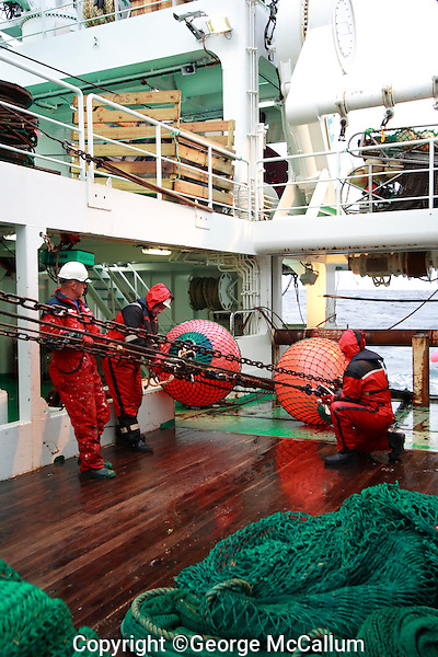Deckhands supervising pelagic fishing net being being hauled in on trawl deck