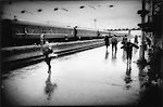 En route through Siberia to Vladivostok, Russia.  Young girls fires off the bird on a rainy train platform along the Trans-Siberia Railway, Slyudyanka, Russia.
