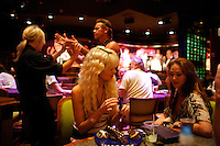 Paris Hilton and Angelina Jolie impersonators enjoy dessert at a hypnotism show in Universal Studios while a hypnotised Arnold Swarzenegger tries to smell a waitress' hair during the Sunburst.Convention of Professional Tribute Artists