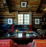 Faux chinked walls combined with a wooden coffee table, drawings  by Tonio Trzebinski and sheepskin rugs create an African and Alpine influenced living room
