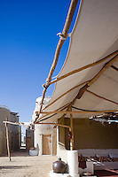 Cotton awnings stretched on palmwood frames shield a covered terrace from the strong Egyptian sun