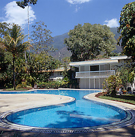 The curved swimming pool gently connects the lush garden with the house designed by architect Gio Ponti in this quiet corner of Caracas