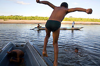 Children play on a canoe in Agua Rico river in the Cofan village of Dureno, near Lago Agrio. They are both from the Cofan indigeneous group. The Cofan feel that Texaco/Chevron are responsible for the sickness and death that followed the spills of crude oil and waste left behind by Texaco's operations in the region. A class action lawsuit was brought against US multinational oil giant Texaco (acquired by Chevron in 2001) by more than 30,000 Ecuadorians. The case has been in the Ecuadorian courts since 2003 and relates to the dumping of billions of gallons of toxic materials into unlined pits and Amazonian rivers. In February 2011 the court ruled that Chevron should pay a fine totalling 9.5 billion USD. However, Chevron has stated that the ruling is 'illegitimate and unenforceable' and has started numerous counter proceedings in US courts. There is some doubt as to whether it will be possible to force Texaco to pay the fine.