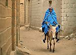 A woman rides a donkey in Timbuktu, a city in northern Mali which was seized by Islamist fighters in 2012 and then liberated by French and Malian soldiers in early 2013.