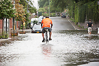 A man rides his bicycle through a rain water flooded section of 12th Avenue in Hamilton Heights, New York City, NY, USA shortly after tropical storm Irene passed over the city, 28 August 2011.