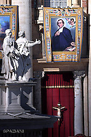 """A tapestry hanged on the facade of St Peter's basilica shows a portrait of French Salomon Leclercq during a canonization mass.Pope Francis  leads a canonization mass on October 16, 2016 at St Peter's square in Vatican. Pope Francis canonises Argentine """"gaucho priest"""" Jose Gabriel Brochero today along with six others raised to sainthood : Salomon Leclercq, Jose Sanchez del Río, Manuel Gonzalez Garcia, Lodovico Pavoni, Alfonso Maria Fusco and Elizabeth of the Trinity."""
