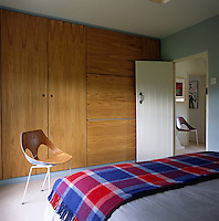 A built-in wooden wardrobe and cupboards by Matthew Lewin in the bedroom acts as a backdrop for the Jason chair, one of a pair by Frank Guille