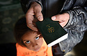 TRAUMA HEALING CASE STUDIES IN LEBANON . REFUGEE FAMILY OF MOUSA AND FATHIA. MOUSA HOLDS A COPY OF THE BIBLE WITH SIX YEAR OLD MYSAA, IN THE TRIUMPHANT MERCY REFUGEE CAMP, ZAHLE, CLOSE TO THE SYRIAN BORDER, IN LEBANON. 20/04/16, PHOTO BY CLARE KENDALL.