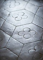 A detail of the bathroom floor highlighting the original concrete tiles which have been laid in a simple geometric pattern