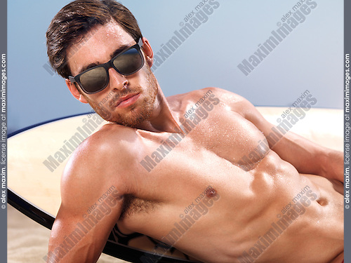 Portrait of a young man in sunglasses with a surfboard lying at the beach