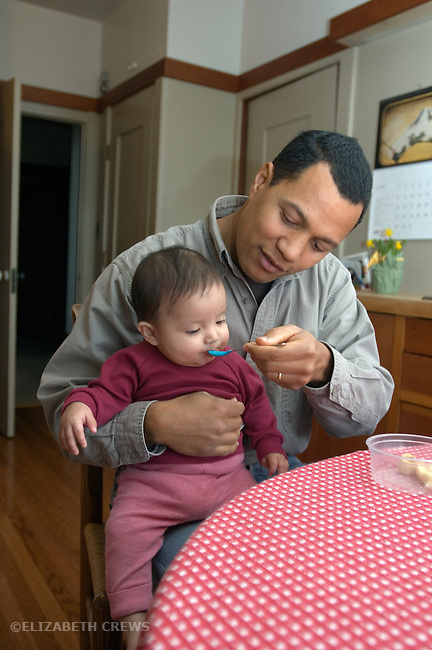 Berkeley CA Adoptive Cuban father feeding nine-month-old daughter  MR