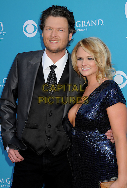 BLAKE SHELTON & MIRANDA LAMBERT.45th Annual Academy Of Country Music Awards held at the MGM Grand Garden Arena, Las Vegas, NV, USA..April 18th, 2010.half length blue dress grey gray suit jacket waistcoat couple sequined low cut plunging neckline cleavage sequins .CAP/ADM/BP.©Byron Purvis/AdMedia/Capital Pictures.