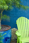A colorful and graphically composed close up detail of a chartreuse green Adirondack chair backed by a blue wall, reminiscent of a Caribbean patio, and a lace leaf Japanese maple in a matching azure-glazed pot to the side.