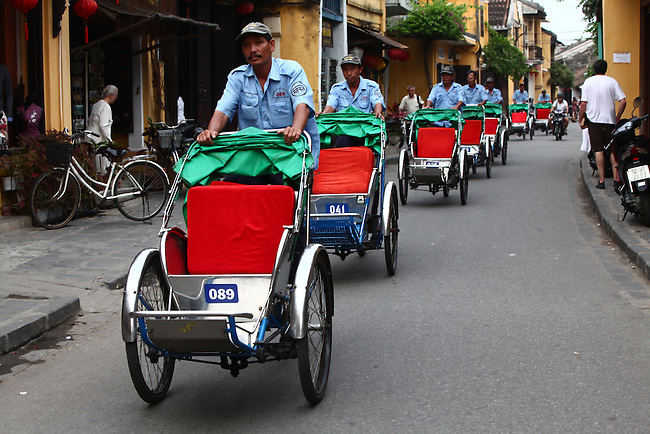 A column of cyclo drivers peddles down a street in Hoi An, Vietnam. Pedicabs such as these are a popular method for tourists to travel around the narrow streets of the quaint colonial city. April 22, 2012.