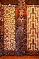 Carved Traditional Maori Figure, called Poupou, supporting the overhead rafters of the meeting house.  This is the seventh on the left side after entering the house.  It shows a marakihau, a mythical sea-creature with a fish-like body, representing the Mataatua tribes of Urewera and Whakatane.  Te Whare Runanga, built 1940, Waitangi Treaty Grounds, Paihia, north island, New Zealand.  The woven panels on either side of the poupou are called tukutuku.  These are comprised of vertically-placed toetoe reeds (kakaho) across which lie narrow laths (kaho), laced through with colored strips of pingao grass and kiekie.