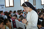 Sister Noora Sabah prays with children preparing for first communion in a church in a displaced persons camp in Ankawa, near Erbil, Iraq. Sabah is a member of the Dominican Sisters of St. Catherine of Siena, who were displaced by ISIS in 2014.