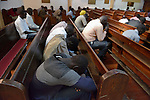 Participants bow their heads in prayer during a worship service of Nuer refugees from South Sudan who live in Cairo, Egypt. The service took place at St. Andrews United Church of Cairo.