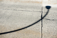 Curved shadow of a lamp post on a cement street