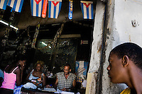 A Cuban boy looks into a empty state shop decorated with Cuban flags, Havana, Cuba, 15 August 2008. About 50 years after the national rebellion, led by Fidel Castro, and adopting the communist ideology shortly after the victory, the Caribbean island of Cuba is the only country in Americas having the communist political system. Although the Cuban state-controlled economy has never been developed enough to allow Cubans living in social conditions similar to the US or to Europe, mostly middle-age and older Cubans still support the Castro Brothers' regime and the idea of the Cuban Revolution. Since the 1990s Cuba struggles with chronic economic crisis and mainly young Cubans call for the economic changes.