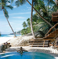 A private pool in the shade of dipping palm trees with the white beach and the ocean beyond