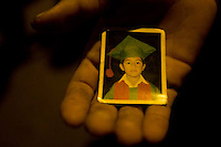A street child shows off one of his few possessions--a photograph of his younger brother in an elementary school graduation uniform.