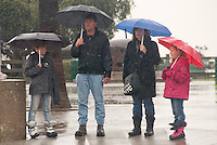 A family takes cover from the rain under their umbrellas on the corner of Ocean Avenue and Colorado Blvd. on Tuesday, December 21, 2010.