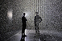 London, UK. 03.10.2012. Random International's experimental, interactive artwork RAIN ROOM opens to the public in The Curve art gallery space at The Barbican Centre. Picture shows: One of the artists, Florian Ortkrass, in the Rain Room, with a friend. Photo credit: Jane Hobson.