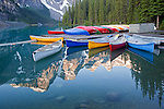 Mountains surrounding Moraine Lake reflect into calm waters as canoes rest on the dock and in the lake, Banff National Park, Alberta, Canada
